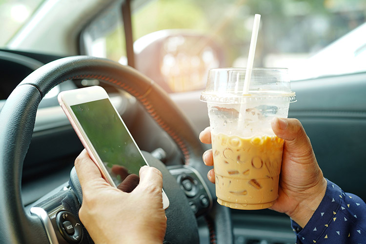 person drives with cellphone in one hand and beverage in the other